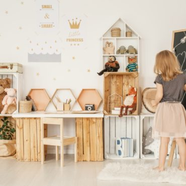 Little girl drawing on a blackboard in her room with wooden boxes, teddy bears and wall stickers