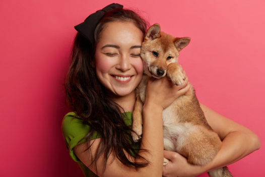 Happy woman pet owner holds cute dog near face, carries shiba inu puppy, smiles pleasantly, enjoys sweet moment, isolated over pink background. Friendship between human and animal. Best friends